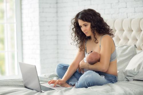 Parent sat on bed breastfeeding while using laptop